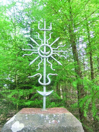 Į akmenį įtaisytas baltiškasis kryžius, kuriame senovinė simbolika: saulės, mėnulio, pasaulio medžio ženklai.
