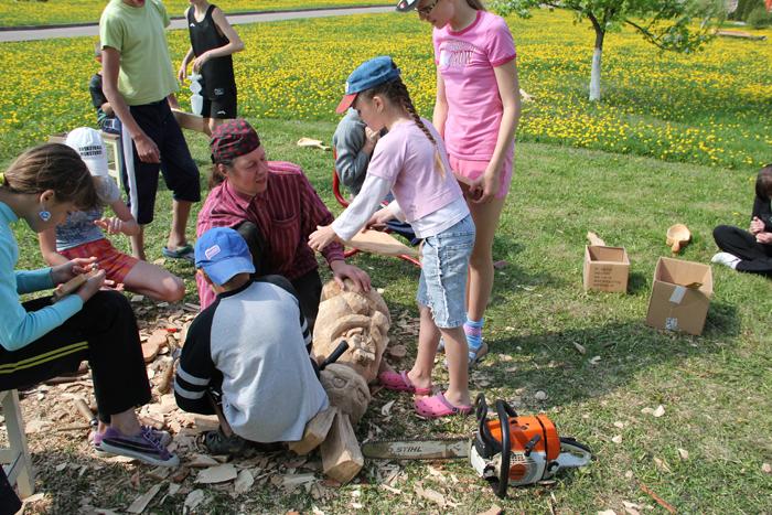 Vaikai dalyvauja mažajame medžio drožėjų plenere.