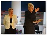 Lietuvos socialinės apsaugos ir darbo ministrė AlgimantaPabedinskienė (dešinėje), prisiminusi ilgalaikį įspūdį jai padariusį vienos marijampolietės likimą, už tai dėkojo A. Blauzdžiūnienei ir staiga pamatė salėje sėdinčią tą pačią marijampolietę, po savo gyvenimo problemų laikotarpio tapusią teisininke.